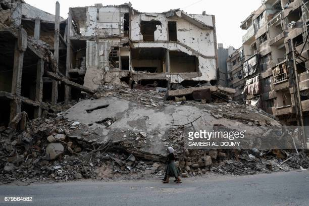 TOPSHOT Syrian girls walk past destroyed buildings in the rebelheld town of Douma on the eastern outskirts of Damascus on May 6 2017 Fighting...