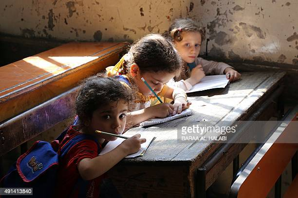 Syrian girls write in a classroom on October 4 2015 at a primary school in the northern city of Aleppo as the new school year starts AFP PHOTO /...