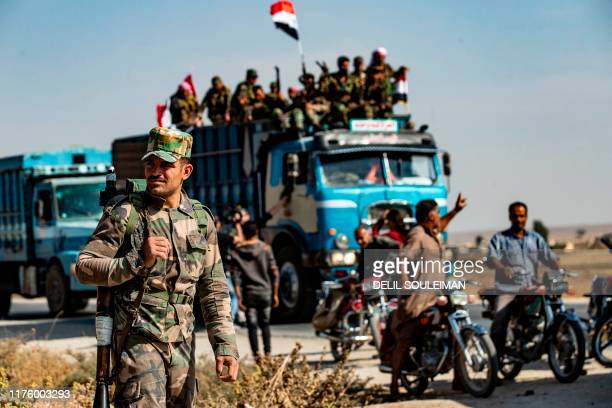 TOPSHOT Syrian government forces arrive in the town of Tal Tamr not far from the flashpoint Kurdish Syrian town of Ras alAin on the border with...