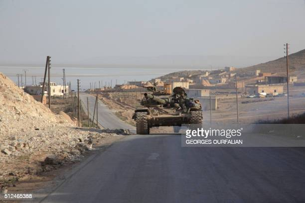 Syrian government forces drive a tank on a road during a military operation against the Islamic State group in the villages of Zarour and Khanaser in...