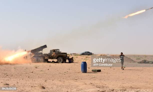 TOPSHOT Syrian government forces fire a multiple rocket launcher from a position in Kobajjep area on the southwestern outskirts of Deir Ezzor on...