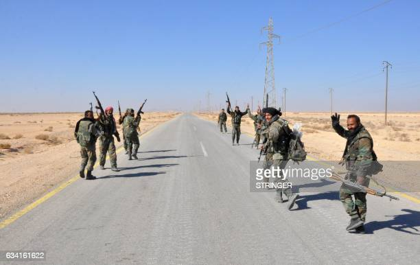 TOPSHOT Syrian government forces flash the sign for victory as they approach the strategic Jihar oil fields on the eastern outskirts of Homs on...