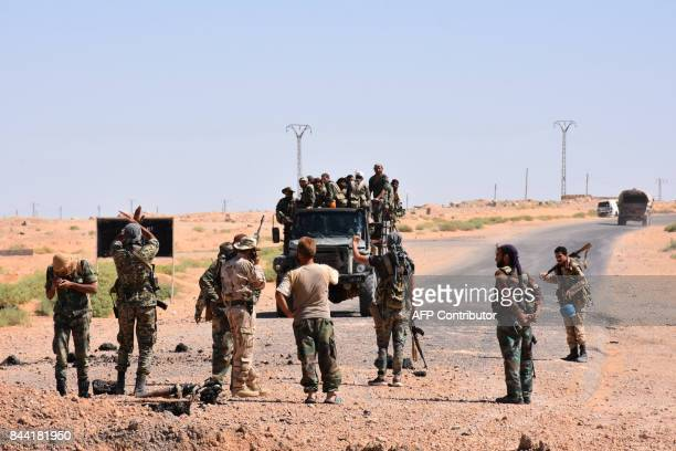Syrian government forces gesture and inspect the site as they arrive to a destroyed bridge on a road between the Kabajeb and AlShula on the...