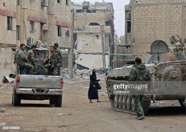 TOPSHOT Syrian government forces' infantry fighting vehicles and trucks drive past damaged buildings down a street in the Eastern Ghouta town of...