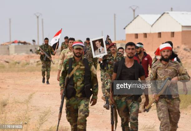 Syrian government forces raise a national flag and an image of President Bashar al-Assad at Tabqa air base in norther Syria's Raqa region on October...