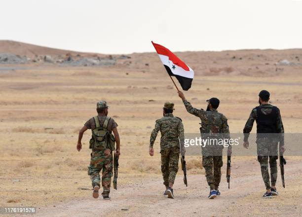 Syrian government forces raise their national flag at Tabqa air base in norther Syria's Raqa region on October 16, 2019. - Syrian President Bashar...