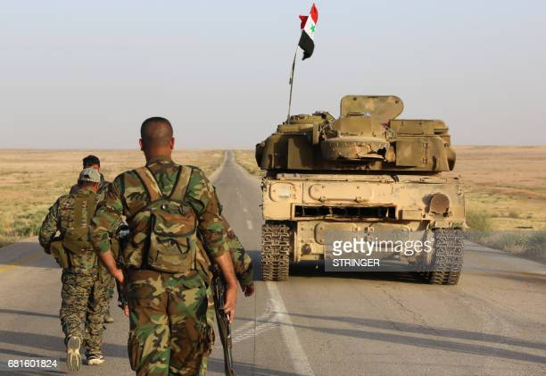Syrian government forces secure a road for a military convoy in the desert area of Saba' Biyar in southeastern Syria near the border with Iraq on May...