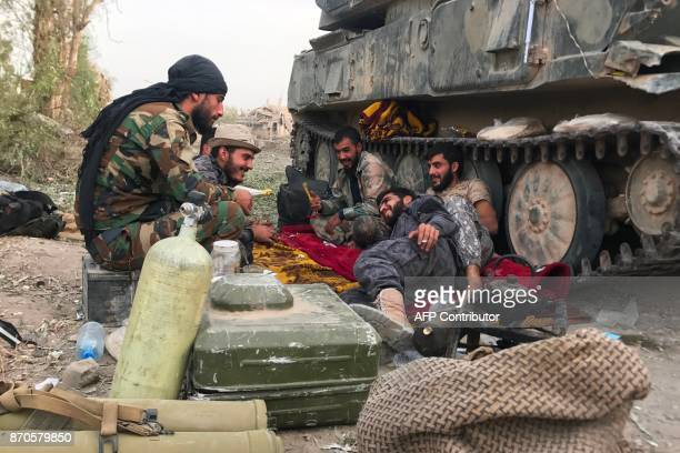 Syrian government forces sit next to an armoured vehicle in a northeastern district of Deir Ezzor on November 5 after retaking the city from Islamic...