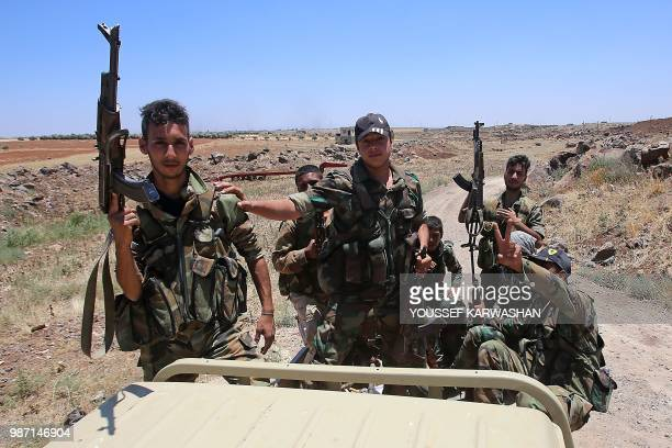 Syrian government forces' soldiers hold their weapons at the back of a pickup truck during a government guided tour in the village of alSourah...