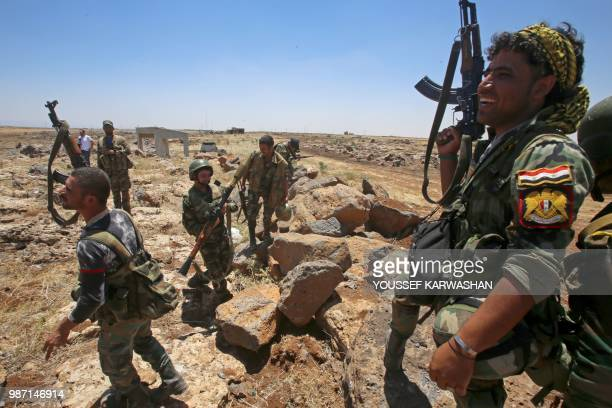 Syrian government forces' soldiers hold their weapons during a government guided tour in the village of alSourah province of Daraa on June 29 2018...