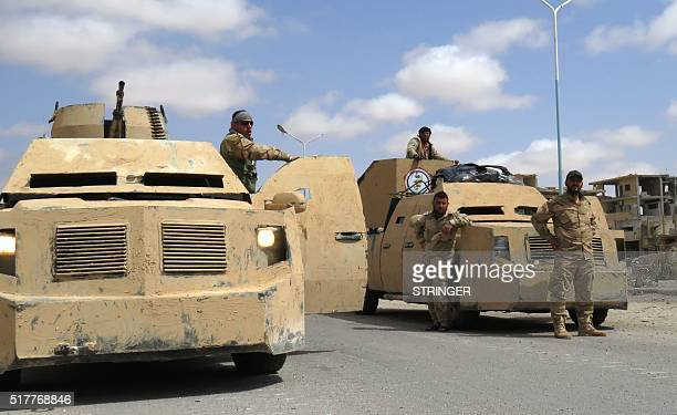 Syrian government forces stand in military vehicles in the ancient city of Palmyra after they recaptured the UNESCO world heritage site from the...