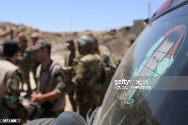 Syrian government forces talk next to a sticker representing the Syrian president Bachar al-Assad during a government guided tour in the village of...