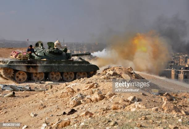 A Syrian government forces' tank fires rounds in the eastern city of Deir Ezzor during an operation against Islamic State group jihadists on November...