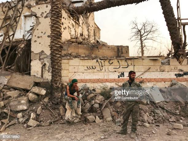 Syrian government forces wait next to a damaged building in a northeastern district of Deir Ezzor on November 5 after retaking the city from Islamic...