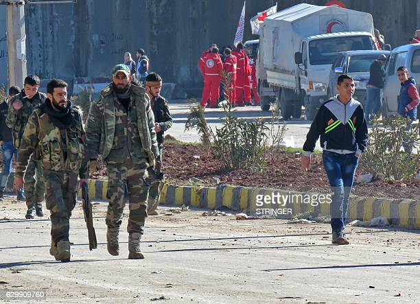 Syrian government forces walk in the embattled city of Aleppo before the start on an evacuation operation of rebel fighters and their families from...