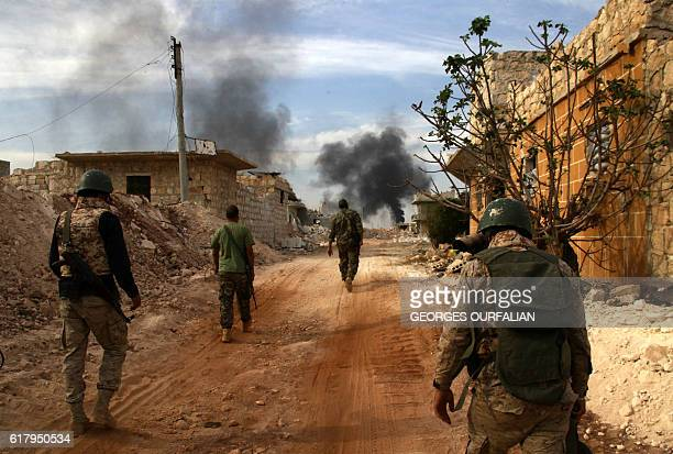TOPSHOT Syrian government forces walk in the strategic area of the Bazo hilltop north of Khan Tuman on the southern outskirts of the northern...