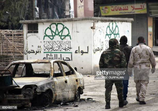 Syrian government forces walk past a destroyed vehicle and a graffiti bearing the emblem of the Ahrar AlSham's Rahman Brigade of the Islamic Front in...