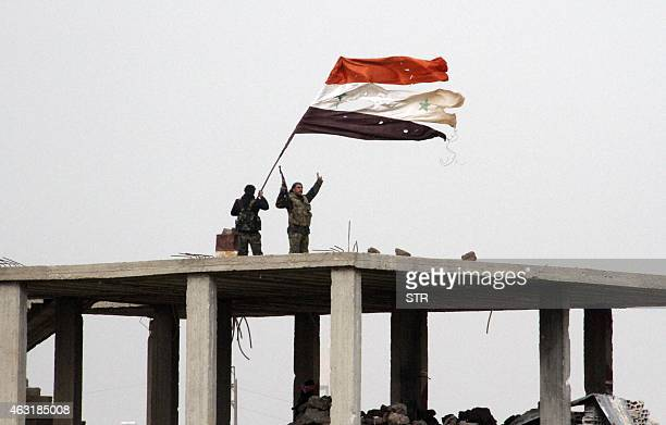 Syrian government forces wave the Syrian flag while standing on top of a building in Deir alAdas in the Daraa province on February 11 2015 after...