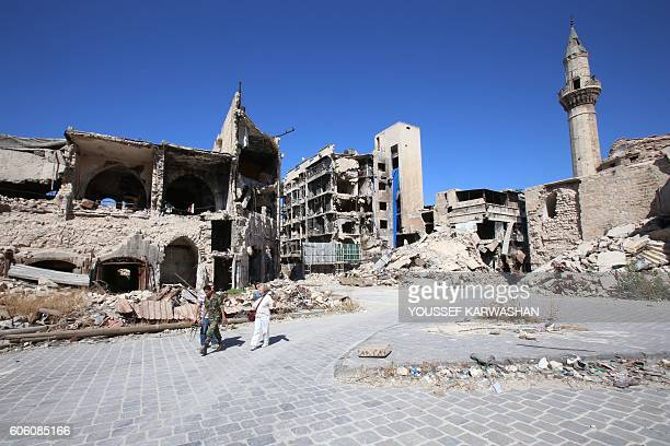 A Syrian government soldier and unidentified people walk in the damaged Khan alWazir market in the governmentheld side of Aleppo's historic city...