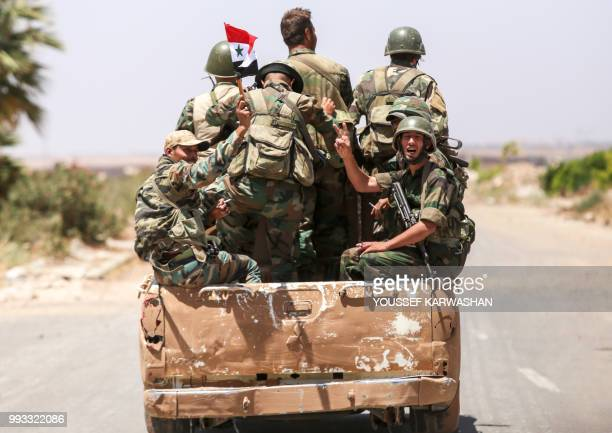 A Syrian government soldier flashes the victory gesture while riding in the back of a pickup truck with comrades at the Nassib border crossing with...