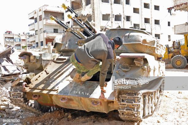A Syrian government soldier jumps into an anti aircraft armored vehicle in Al Hajar al Aswad on April 22 during a regime offensive targeting the...