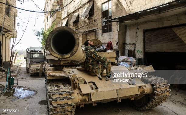A Syrian government soldier sits on a tank stationed on the edges of the town of Zamalka in Eastern Ghouta on the outskirts of the Syrian capital...