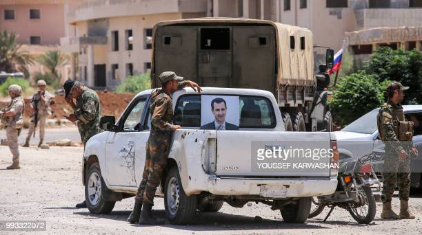 Syrian government soldier stands next to a pickup truck bearing the image of President Bashar al-Assad at the Nassib border crossing with Jordan in...