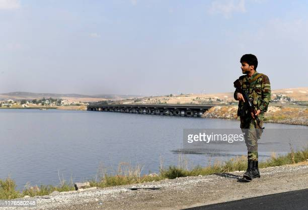 Syrian government soldier walks along the bank of the Euphrates river near the Qarah Qozak bridge in the north of Aleppo governorate near the border...
