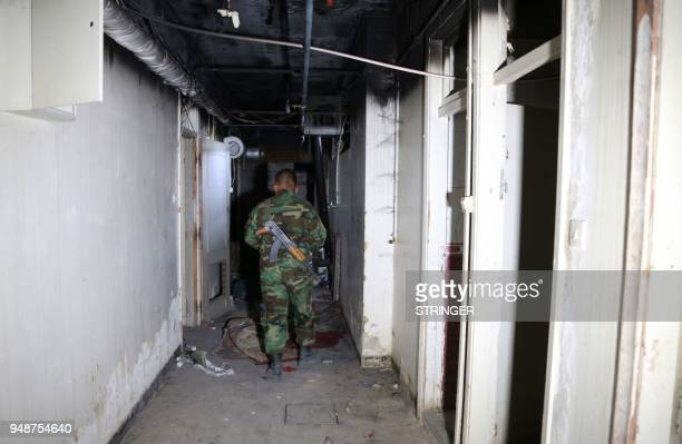 A Syrian government soldier walks in abandoned underground prison used by Jaish alIslam fighters in the former rebelheld Syrian town of Douma on the...