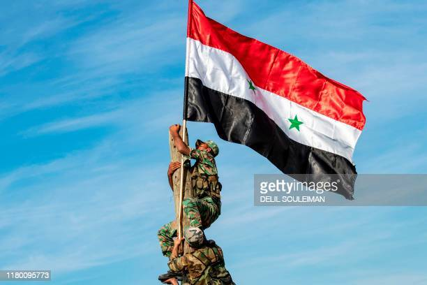 Syrian government soldiers climb up a wooden pole with a Syrian government national flag while deploying for the first time in the eastern...