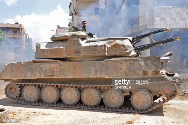 Syrian government soldiers drive an anti aircraft armored vehicle in Al Hajar al Aswad on April 22 during a regime offensive targeting the Islamic...