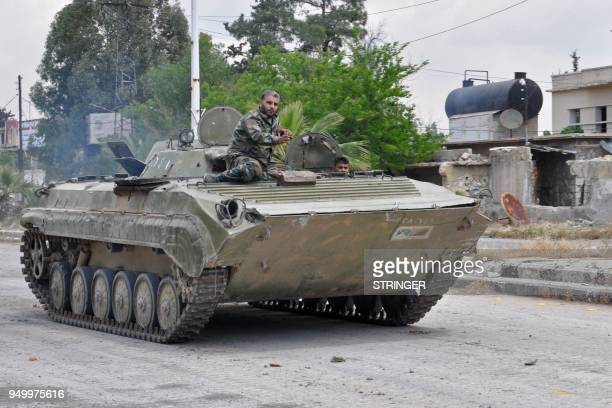 Syrian government soldiers drive an armored personal vehicle in Al Hajar al Aswad on april 22 during a regime offensive targeting the Islamic State...