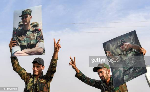 Syrian government soldiers hold up portraits of President Bashar al-Assad while flashing the victory gesture at a position on the outskirts of the...