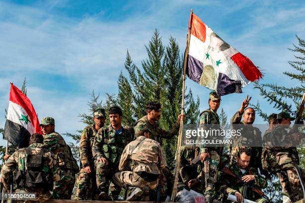 Syrian government soldiers pose with a Syrian government national flag defaced with a portrait of President Bashar al-Assad while deploying for the...