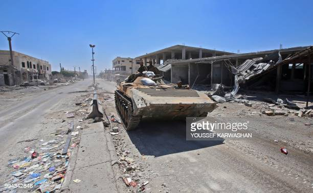TOPSHOT Syrian government soldiers ride in an infantryfighting vehicle in the town of Saida in the west of Daraa province on July 7 2018