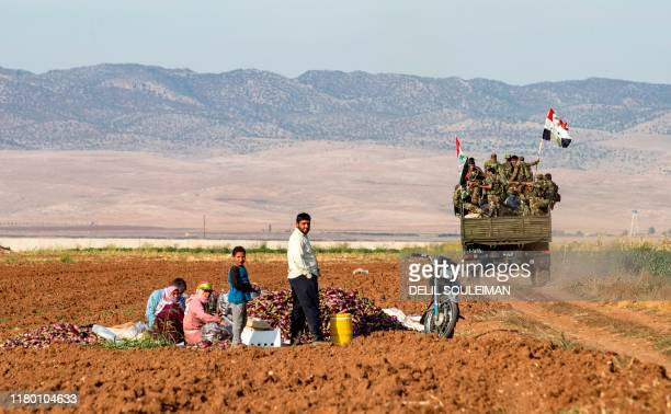 Syrian government soldiers ride in the back of a truck with national flags past people sitting in a field with harvested aubergines, as government...
