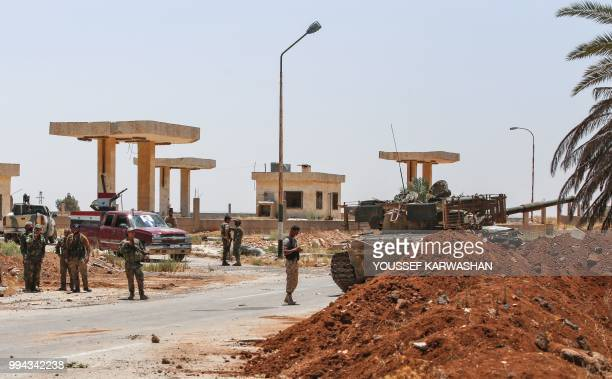 Syrian government soldiers stand by a tank and armed pickup trucks at the Nassib border crossing with Jordan in the southern province of Daraa on...