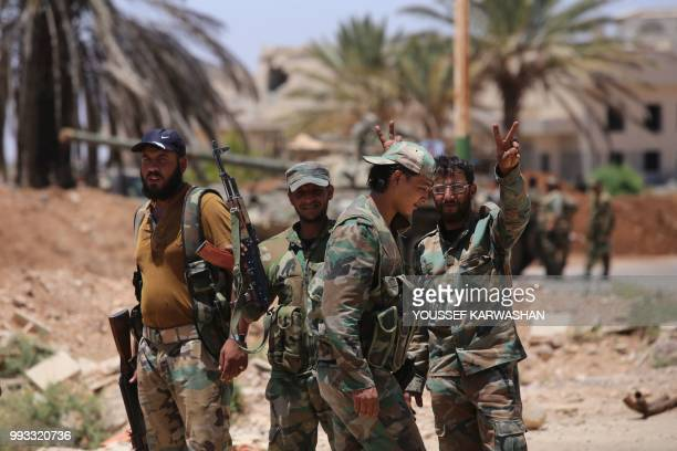 Syrian government soldiers stand flashing the victory gesture at the Nassib border crossing with Jordan in the southern province of Daraa on July 7,...
