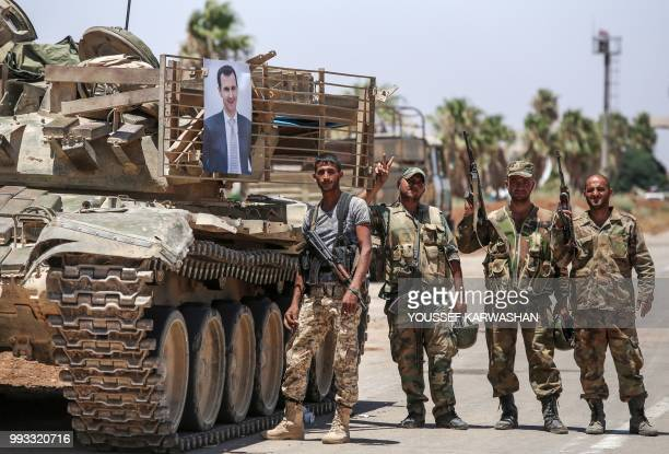 Syrian government soldiers stand flashing the victory gesture next to a picture of Syrian President Bashar al-Assad hanging on a tank at the Nassib...