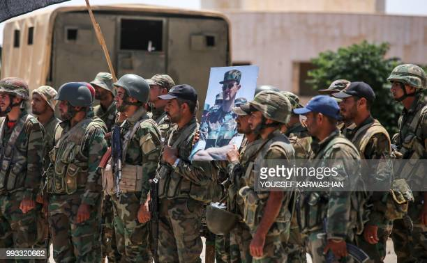 Syrian government soldiers stand holding a picture of Syrian President Bashar al-Assad dressed in a Field Marshal's camouflage fatigues at the Nassib...