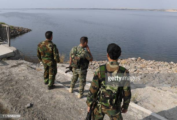 Syrian government soldiers walk along a road on the bank of the Euphrates river near the Qarah Qozak bridge in the north of Aleppo governorate near...