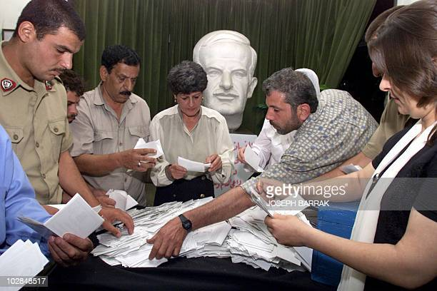 Syrian government staff count the ballots of the presidential plebiscite in front of a bust of Syria's late president Hafez alAssad in a Damascus...