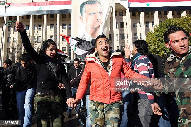 Syrian government supporters dance in front of a poster of Syrian President Bashar alAssad during a proregime rally in Damascus on January 27 2012...