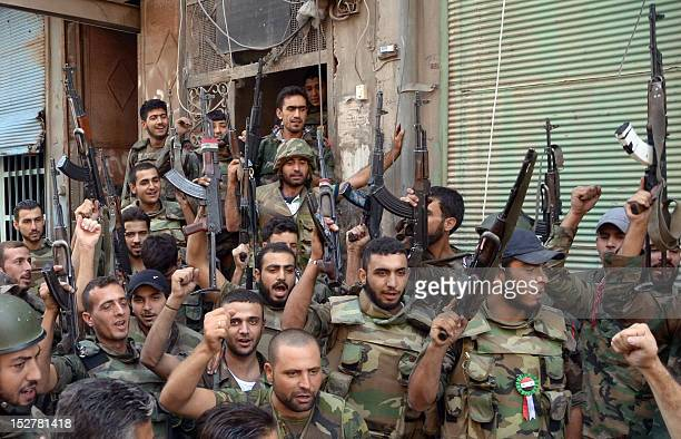 Syrian government troops hold up their rifles on September 25 in the northern Syrian city of Aleppo following fighting between the troops and rebel...