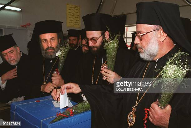 Syrian Greek Orthodox bishops cast their presidential votes at a polling station in Damascus 10 July 2000 holding flowers given by young supporters...