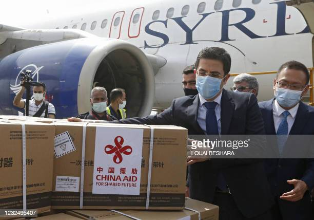 Syrian Health Minister Hassan al-Ghabash and the Chinese Ambassador Feng Biao oversee the unloading of aid boxes containing the Sinopharm Covid-19...