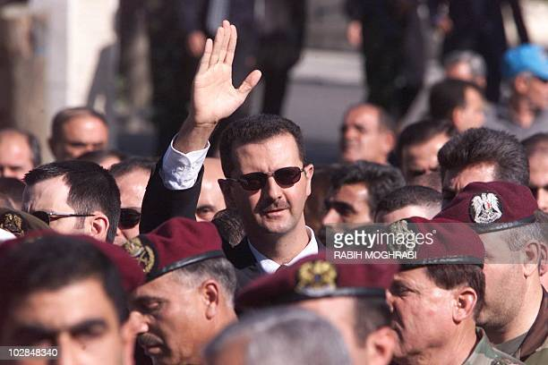 Syrian heir apparent Bashar alAssad waves to supporters as he marches behind the coffin of his father Syrian President Hafez alAssad during his...