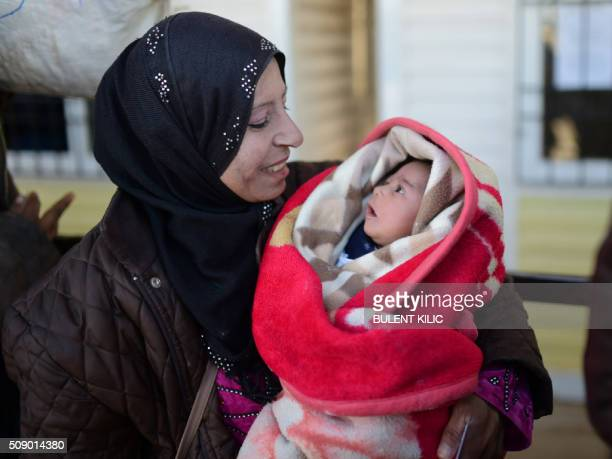 A Syrian holds a baby as she waits with others to return to Syria on February 8 2016 at the Turkish Oncupinar border gate near Kilis southerncentral...