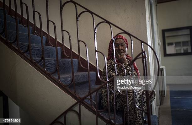 Syrian Huriye Mustapha who fled Syrian city of Aleppo two years ago after deaths of her husband and 2 brothers sits on the stairs at a hotel in...