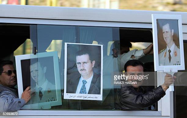 Syrian intelligence officers display pictures of their president Bashar alAssad on their way out from Lebanon at the Masnaa border crossing point 25...